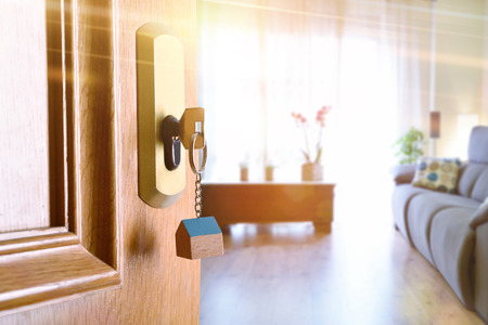 Photo pour Open entrance door detail of a house with keys in the lock and furnished living room in the background with golden light effect. - image libre de droit