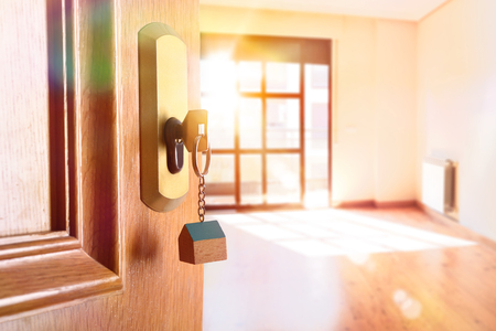 Photo for Open entrance door detail of a house with keys in the lock and empty room in the background with golden light effect. Lateral view - Royalty Free Image
