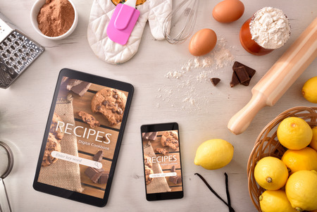 Photo for Devices with online recipes app and pastry ingredients background. Use of the digital devices to cook. Concept of recipes in digital book. Horizontal composition. Top view - Royalty Free Image