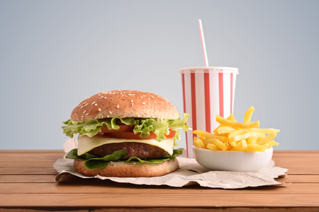Foto de Beef burger,chips and soda on wooden table with golden backgorund. Front view. Horizontal composition. - Imagen libre de derechos