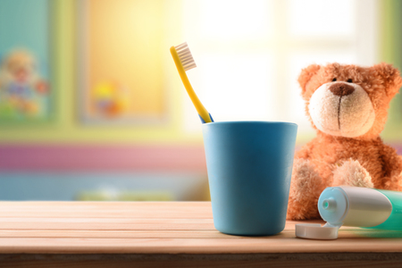 Foto de oral hygiene for children in children's room with cleaning elements on wooden table and stuffed toy. Horizontal composition. Front view - Imagen libre de derechos