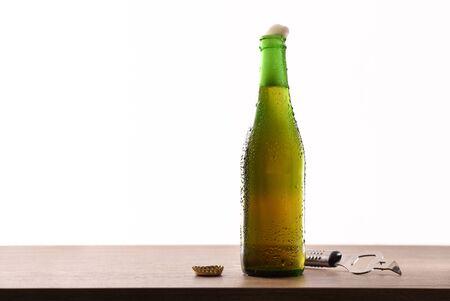 Photo pour Green glass bottle with sparkling liquid and white background. Horizontal composition. Front view. - image libre de droit