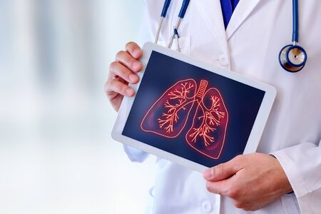 Photo pour Doctor showing a picture of lungs on a tablet in a hospital. Horizontal composition. - image libre de droit