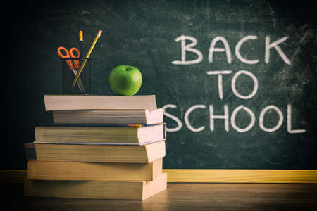 Photo pour Stack of books with pencil and apple on class table with green chalkboard in background with back to school message. Concept of studying. - image libre de droit