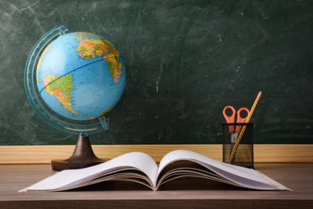 Photo pour Book and pen with pencil and scissors and achool globe on desk with green blackboard in the background. Concept of studying. - image libre de droit