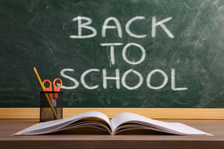Book and pen with pencil and scissors on school desk with blackboard background with message back to school.