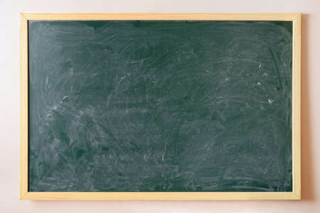 Photo for Green chalk dirty college blackboard with wooden frame hanging on the wall - Royalty Free Image