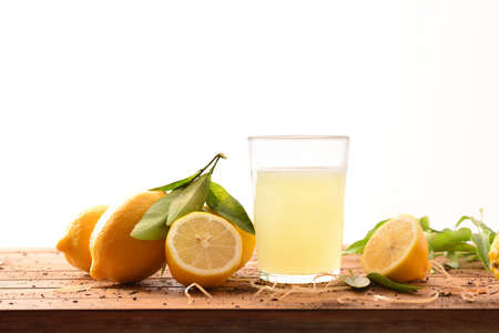 Photo for Freshly squeezed juice on a wooden table full of lemons isolated background. Front view. Horizontal composition. - Royalty Free Image