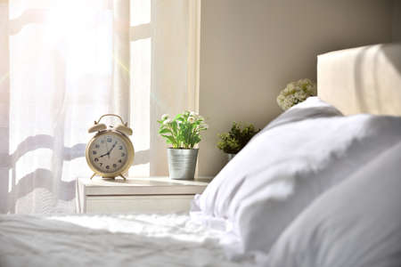 Photo pour Sunny sleeping room without people with white bedding in the morning with decorated table with alarm clock and plants with window with sunbeam - image libre de droit
