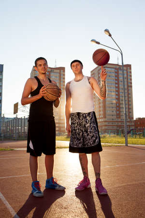 Two guys are sitting on the basketball court.