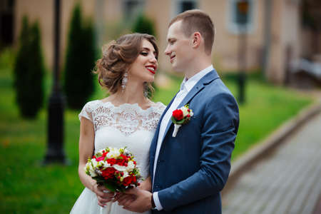 Photo for Bride and groom on their wedding day, walking outdoors in nature. - Royalty Free Image