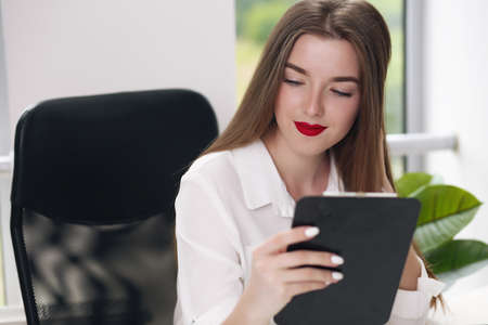 Photo pour Portrait of young businesswoman wearing white shirt sitting in modern office with laptop - image libre de droit