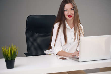 Photo for young brunette businesswoman sitting on bright modern workplace - Royalty Free Image