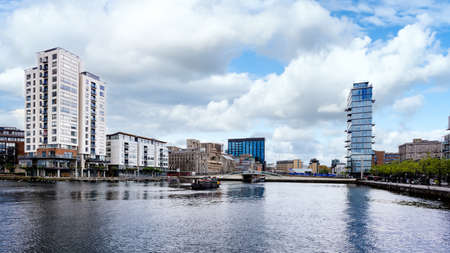 Photo for Cityscape of Dublin Docklands and river Liffey with modern buildings and barge on river. Republic of Ireland - Royalty Free Image