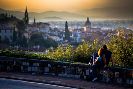 A couple in love - girl and boy sitting on a small wall by the road watching a scenic sunset over a romantic Italian city on the hills in the blurred background; in Florence, Italy