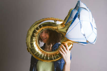 Smiling girl is holding a large balloon in the form of a ring.