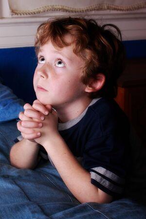 young boy saying his bedtime prayers