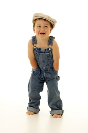 adorable toddler in overalls and a vintage hat