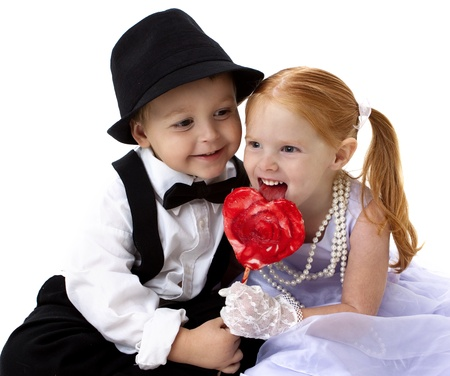 adorable little boy and girl sharing a heart shaped sucker