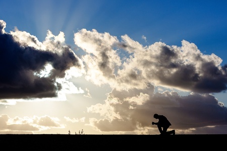 man kneeling in prayer before a dramatic sky