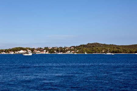 Panoramic shot of island. Croatia. Fishing boat in front.