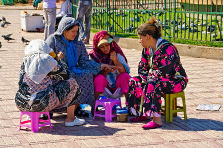 CASABLANCA, MOROCCO - OCTOBER, 16, 2010: Women on main square in Casablanca putting henna on a hands. Henna has been used to adorn young women's bodies as part of social and holiday celebrations