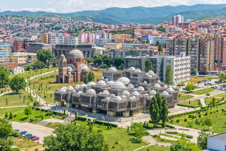 PRISTINA, KOSOVO - JULY 01, 2015: Aerial view of capital city with some old buildings like National Public Library and Christ the Saviour Cathedral.