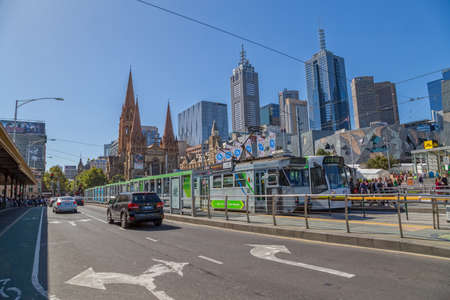 MELBOURNE, AUSTRALIA - MARCH 21, 2015: Trams on Flinders Street tram stop near thr Federation Square and Cathedral of Saint Paul on the beautiful sunny day.