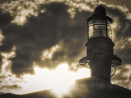 Lighthouse green beacon against cloudy sky