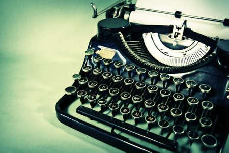 Vintage manual typewriter photographed against a dusky teal background.
