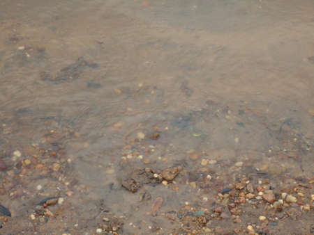 river water on sand and small stones on the coast