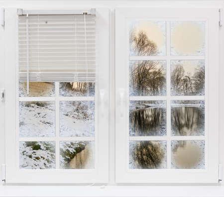 Photo pour view through the frozen window on the winter landscape sun rays - image libre de droit