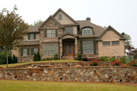 A nice house on a hill over a stone wall