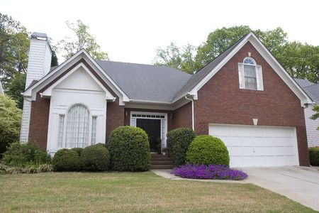 A nice brick house planted with purple flowers
