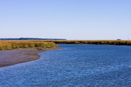 A wetlands marsh with a salt water channel and crystal blue sky