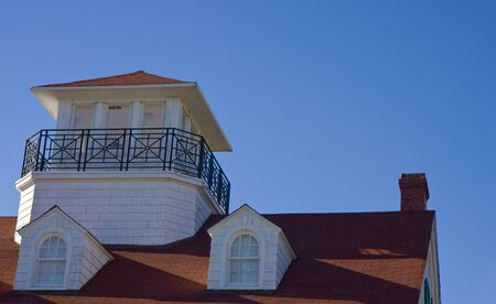 A coastal roofline with a red tile roof on a white house