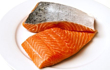 Fresh salmon fillets with skin on a white plate