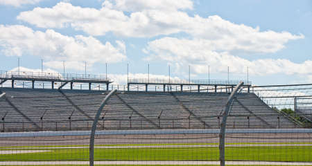 An automobile racetrack between a fence and stands