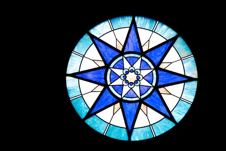 A round blue and white stained glass window on black background