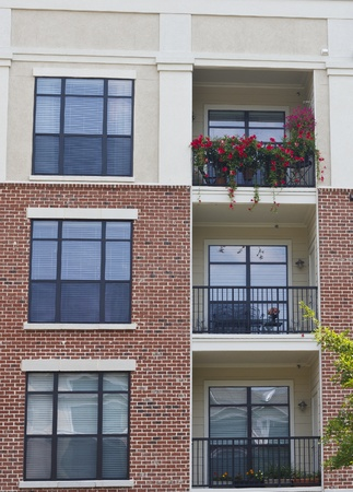 Flowers growing on balconies of brick and stucco condos