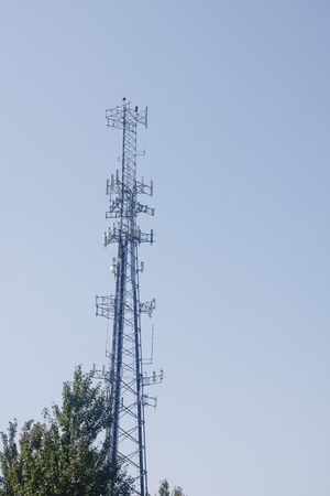 A cell phone tower against a clear blue sky