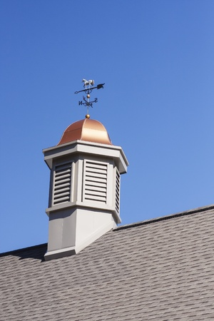 A cupola with copper roof and weather vane on a roof under a clear blue sky