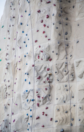 Rock climbing wall with foot and hand holds and ropes for background