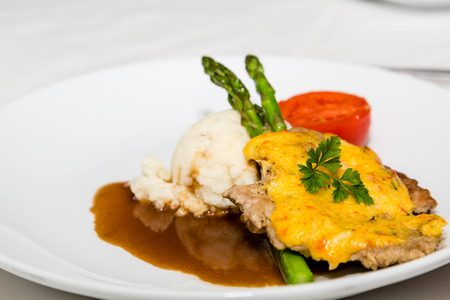 A dinner of baked pork with sauce and gravy with asparagus and mashed potatoes