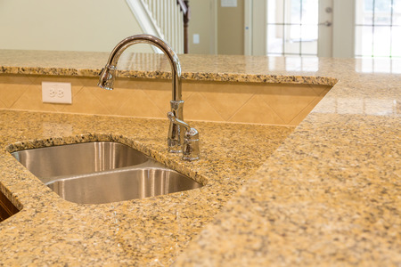 New stainless steel sink in granite countertop in a new home