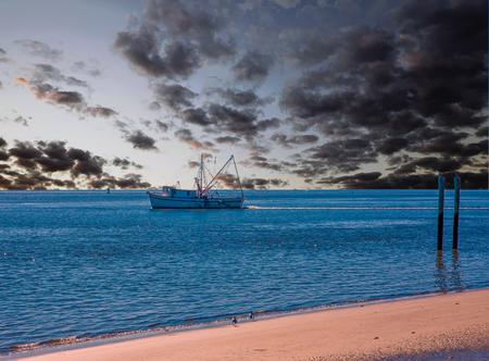 Photo pour Shrimp boat and posts on the beach - image libre de droit