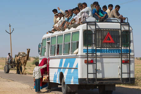 Jamba, India, April 02, 2007 - People enter the intercity bus in Jamba, India. Public transportation buses in the Great Thar desert, Rajasthan are usually overloaded.