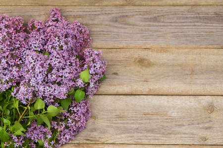 Fresh lilac flowers on the old wooden table.