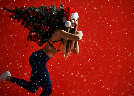 Photo pour sexy Christmas fitness sport woman wearing santa hat holding  xmas tree on her shoulders. running forward on a snowing red background - image libre de droit