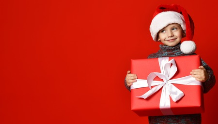 Foto de Smiling funny child in Santa red hat holding Christmas gift in hand over red wall background. Christmas eve concept. - Imagen libre de derechos